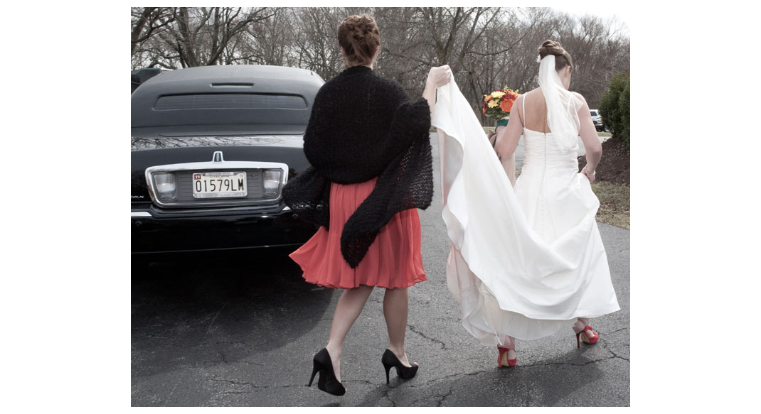 The Maid of Honor helping the bride to the limo